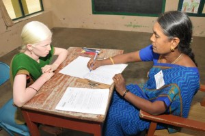 A scribe (secondary grade teacher) writing Plus Two examination for a visually-challenged student at a school.